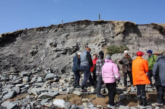 A group of people standing on a pebble beach below an eroded edge containing stonework and different soil deposits