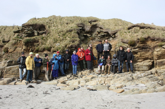 A group of people standing on a beach in front a cliff with the remains of a broch on top