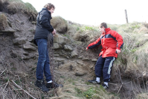 Two boys pointing at a small piece of bone visible in the eroding soil of a coast edge