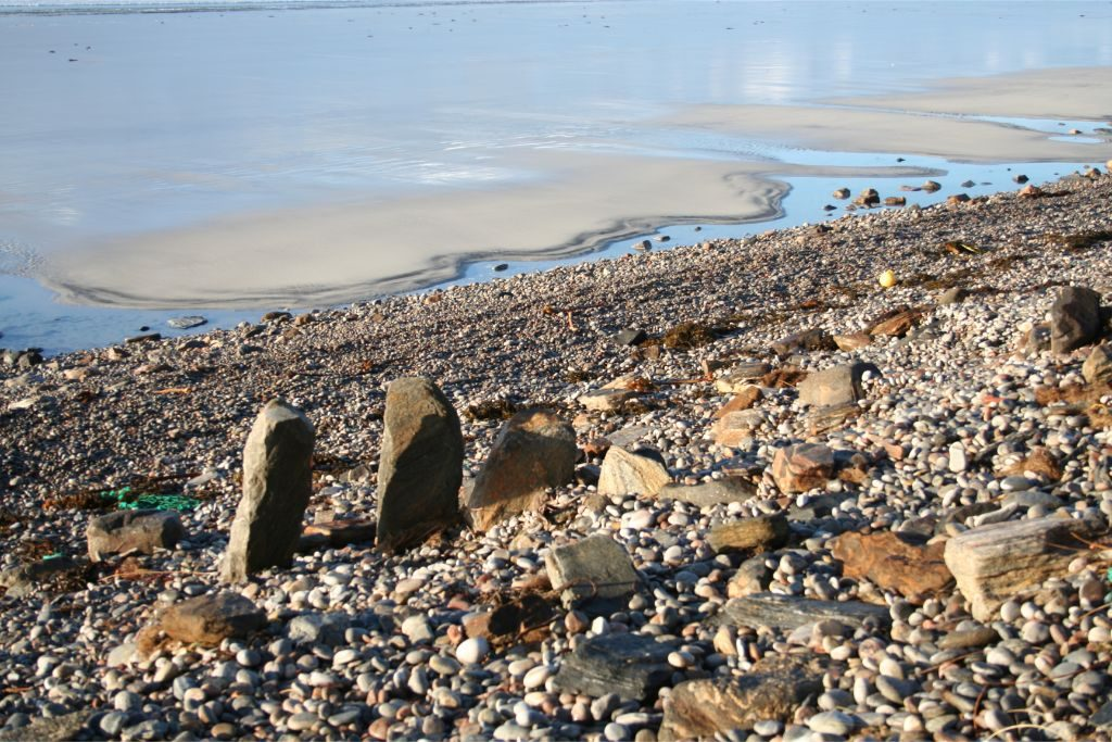 Large upright stone slabs standing in a line on a pebble beach