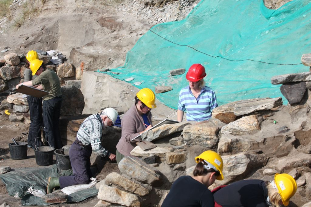 A group of people on an archaeoloical site, drawing and trowelling, surrounded by stone walls and sand
