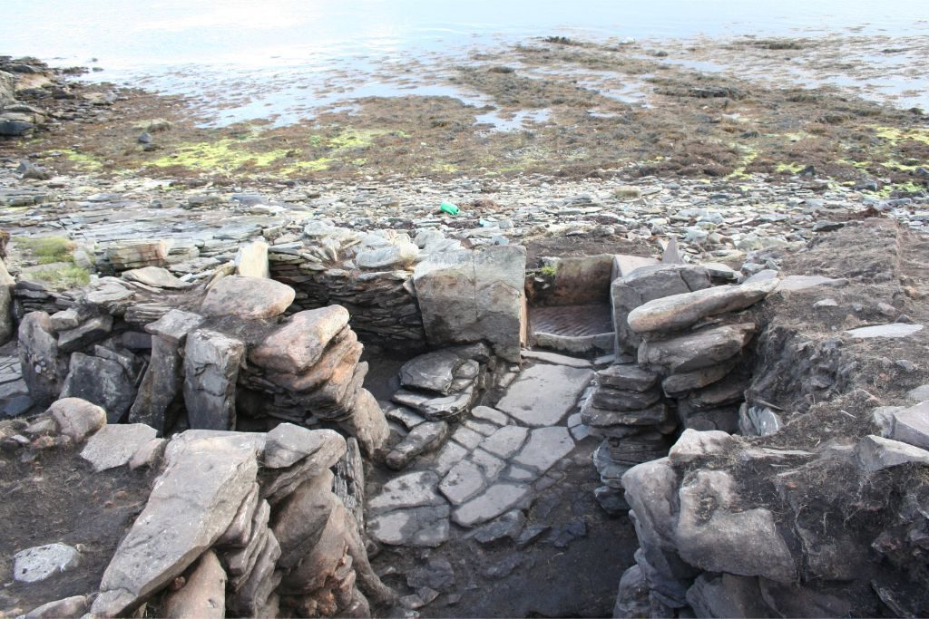 An archaeological site of drystone structures, paved stone surfaces and upright slabs, on a pebble beach with the sea behind