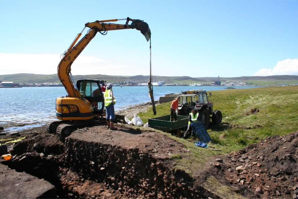 An archaeological trench next to the sea, with a digger lifting a large stone slab onto a trailer and trailer
