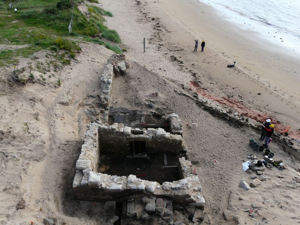 Overhead view of a sandy beach with a ruined rectangular stone building exposed by the excavation of a sand dune, with one corner of the building destroyed