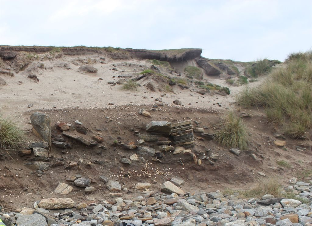 An eroding sandy cliff face on a beach with stone walls and dark layers of soil visible in the section