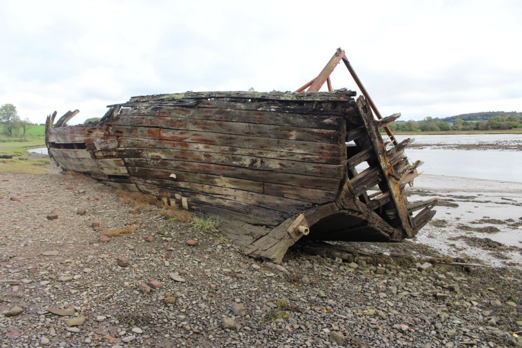 A wooden boat sitting on a mud and pebble riverbank, resting on its starboard side. The planking around the transom and part of the planking of the port side of the hull is gone
