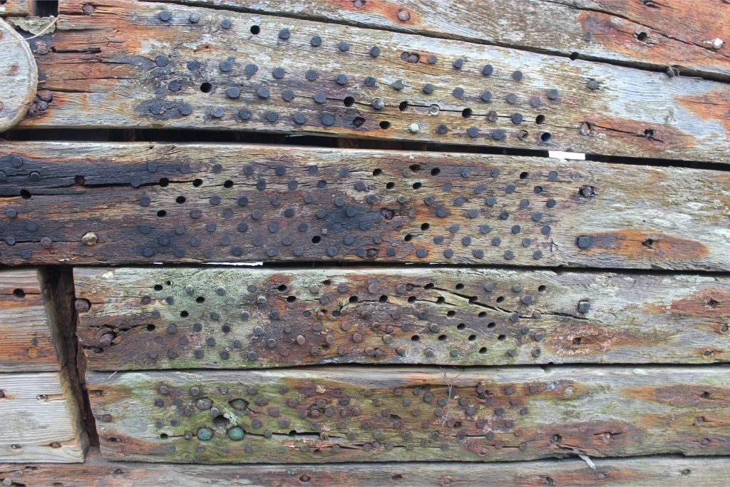 A close up shot of wooden planking of the hull with a grid of small round holes, some filled with wooden pegs