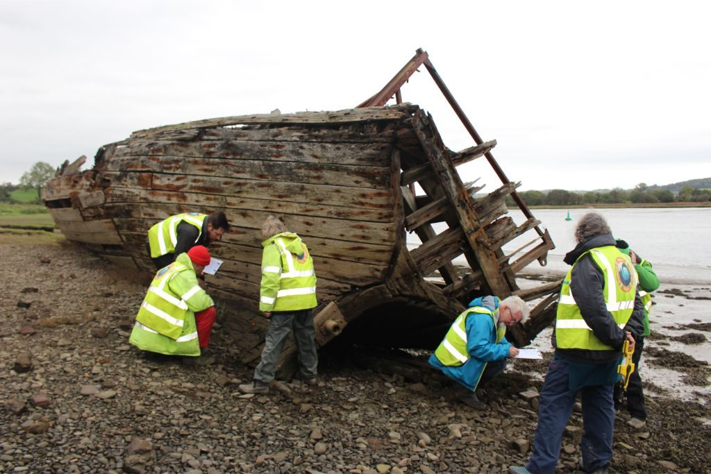 The same wooden boat on the riverbank, with a group of people in hi-vis vests clustered around the stern recording the vessel writing notes and holding tape measures