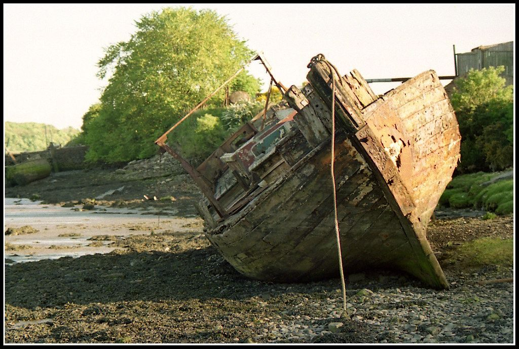 A wooden boat sitting high up on a beach, the view shows the bow and front end, with metal plating around the stem at the front. The iron plating has partly fallen off, the paintwork is peeling and the planking looks slightly rooten. The boat has clearly not been used for some time, but is intact