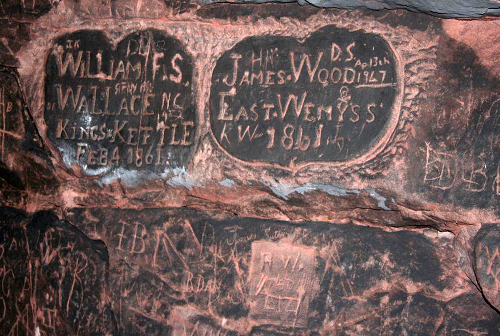 Close-up of two shield shapes carved into the red sandstone wall inside a cave. Lettering of one reads William Wallace, Kingskettle, Feb 4 1861. Lettering on the other reads James Wood, East Wemyss, 1861