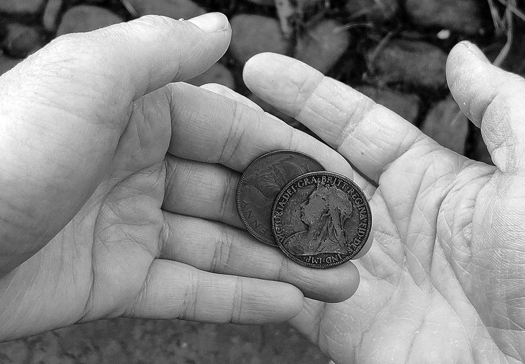 Black and white close up photo of a hand offering two Victorian pennies to another hand