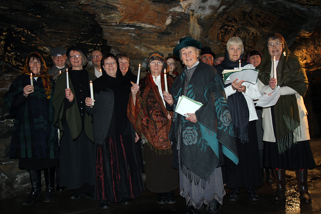 Group of 14 men and women dressed in Victorian clothes standing in a cave, each holding a candle and smiling at the camera