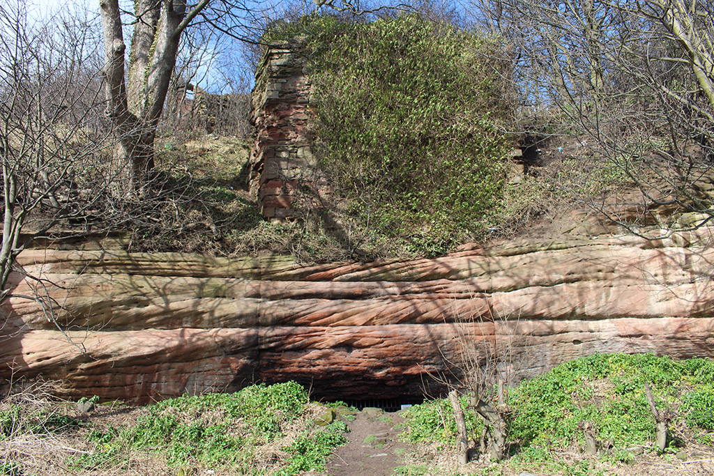 Red sandstone cliff face with ivy covered ruinuous tower at the top and dark almost hidden cave entrance at the base