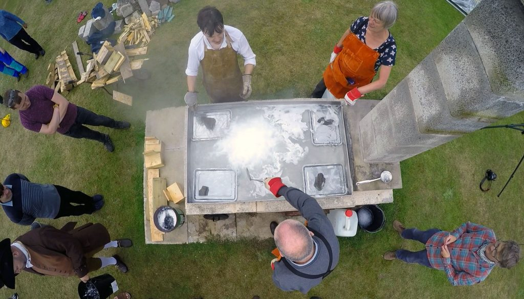 Overhaead view of a large rectangular metal pan, upon a brick support with a chimney at one end, filled with steaming water. Three people stand around it wearing leather aprons. One person stirs the liquid with a metal spatula